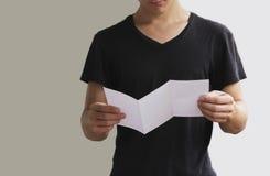 Κενό άσπρο βιβλιάριο φυλλάδιων ιπτάμενων ανάγνωσης ατόμων Παρουσίαση φυλλάδιων Χέρια λαβής τευχών Το άτομο παρουσιάζει σαφές έγγρ Στοκ Φωτογραφία