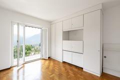 Κενό άσπρο δωμάτιο με το παρκέ και τα μεγάλα παράθυρα στοκ φωτογραφίες με δικαίωμα ελεύθερης χρήσης