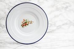Κενό άσπρο εκλεκτής ποιότητας πιάτο σμάλτων με το σχέδιο λουλουδιών Στοκ Φωτογραφία
