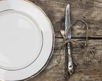 κενό άσπρο κεραμικό πιάτο και εκλεκτής ποιότητας ασημικές στο ξύλινο backgr στοκ εικόνες