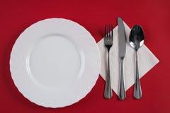 Κενό άσπρο πιάτο γευμάτων με το ασημένιο κουτάλι σούπας δικράνων και επιδορπίων, που απομονώνεται στο κόκκινο υπόβαθρο τραπεζομάν Στοκ Φωτογραφία