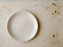 Κενό άσπρο πιάτο στο βρώμικο λεκιασμένο πίνακα Έννοια τριβής Στοκ Εικόνα