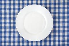 Κενό άσπρο πιάτο στο ελεγμένο τραπεζομάντιλο Στοκ Εικόνα