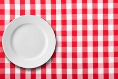 Κενό άσπρο πιάτο στο κόκκινο ελεγμένο τραπεζομάντιλο στοκ φωτογραφία με δικαίωμα ελεύθερης χρήσης