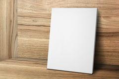 Κενό άσπρο πλαίσιο καμβά που κλίνει στον ξύλινο τοίχο και το ξύλινο πάτωμα, Mo Στοκ Εικόνες