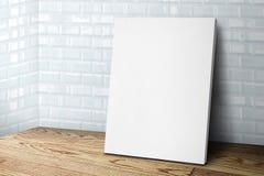 Κενό άσπρο πλαίσιο καμβά που κλίνει στον τοίχο κεραμιδιών και το ξύλινο πάτωμα, Mo Στοκ εικόνες με δικαίωμα ελεύθερης χρήσης