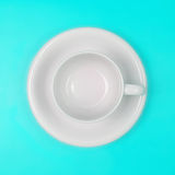 Κενό άσπρο φλυτζάνι καφέ ή τσαγιού στο δονούμενο υπόβαθρο χρώματος Στοκ Φωτογραφία