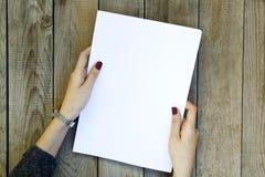 Κενό έγγραφο εκμετάλλευσης χεριών γυναικών για τον ξύλινο πίνακα στοκ εικόνα με δικαίωμα ελεύθερης χρήσης