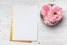 Κενό έγγραφο και χαριτωμένα ρόδινα λουλούδια στον άσπρο ξύλινο πίνακα στοκ φωτογραφία