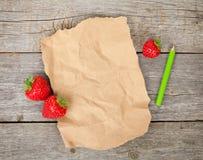 Κενό έγγραφο και ώριμες φράουλες πέρα από το ξύλινο επιτραπέζιο υπόβαθρο Στοκ φωτογραφία με δικαίωμα ελεύθερης χρήσης