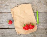 Κενό έγγραφο και ώριμες φράουλες πέρα από το ξύλινο επιτραπέζιο υπόβαθρο Στοκ Εικόνες