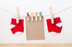Κενό έγγραφο με τις κάλτσες μωρών που κρεμούν στη σκοινί για άπλωμα αγάπης στοκ εικόνες με δικαίωμα ελεύθερης χρήσης