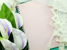 Κενό βιβλίο σημειώσεων που ανοίγει με το ντεκόρ δαντελλών και το τεχνητό calla υπόβαθρο λουλουδιών Στοκ εικόνα με δικαίωμα ελεύθερης χρήσης