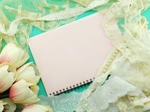 Κενό βιβλίο σημειώσεων που ανοίγει με το ντεκόρ δαντελλών και το τεχνητό υπόβαθρο λουλουδιών τουλιπών Στοκ Φωτογραφία