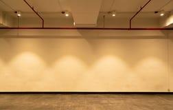 Κενό δωμάτιο και άσπρος τοίχος με τα επίκεντρα Φωτισμένο φως λαμπτήρων Εσωτερικό δωματίων με τον ελαφρύ και ζωηρόχρωμο τοίχο ανώτ Στοκ φωτογραφία με δικαίωμα ελεύθερης χρήσης