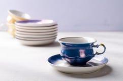 Κενό ζωηρόχρωμο επιτραπέζιο σκεύος πορσελάνης Μπλε φλυτζάνι με το πιάτο στο ιώδες υπόβαθρο Στοκ Φωτογραφία