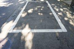 Κενό διάστημα χώρων στάθμευσης στην πόλη με τη σκιά Στοκ Φωτογραφία