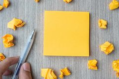 Κενό κίτρινο έγγραφο σημειώσεων με τη μάνδρα εκμετάλλευσης επιχειρηματιών και θρυμματισμένο έγγραφο για το ξύλινο επιτραπέζιο υπό στοκ εικόνες