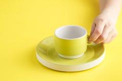 Κενό κίτρινο φλυτζάνι καφέ ή τσαγιού στο κίτρινο υπόβαθρο Στοκ Εικόνες