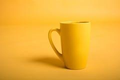 Κενό κίτρινο φλυτζάνι στο κίτρινο υπόβαθρο Κίτρινο κενό κενό κουπών για τον καφέ ή το τσάι Στοκ φωτογραφίες με δικαίωμα ελεύθερης χρήσης