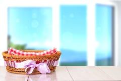 Κενό καλάθι με την πορφυρή κορδέλλα στον ξύλινο πίνακα με τη φωτεινή θαμπάδα στοκ εικόνες