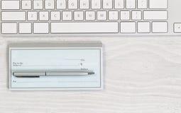 Κενό καρνέ επιταγών με τη μάνδρα στον άσπρο υπολογιστή γραφείου Στοκ Φωτογραφίες