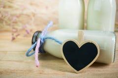 Κενό καλό πλαίσιο καρδιών με τα μπουκάλια γάλακτος στο ξύλινο υπόβαθρο Στοκ Εικόνα