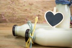 Κενό καλό πλαίσιο καρδιών με τα μπουκάλια γάλακτος στο ξύλινο υπόβαθρο Στοκ εικόνα με δικαίωμα ελεύθερης χρήσης
