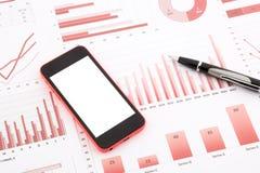 Κενό κινητό τηλέφωνο στις κόκκινες γραφικές παραστάσεις, τα διαγράμματα, τα στοιχεία και την επιχείρηση σχετικά με Στοκ Εικόνα