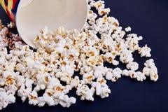 Κενό κύπελλο με popcorn, όλο popcorn που διασκορπίζεται σε ένα μπλε υπόβαθρο Στοκ φωτογραφία με δικαίωμα ελεύθερης χρήσης