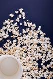 Κενό κύπελλο με popcorn, όλο popcorn που διασκορπίζεται σε ένα μπλε υπόβαθρο στοκ εικόνες με δικαίωμα ελεύθερης χρήσης