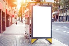 Κενό λευκό που διαφημίζει τον αστικό πίνακα διαφημίσεων κοντά στη στάση λεωφορείου πόλεων, placeholder πρότυπο σε μια οδό, διάστη στοκ εικόνα