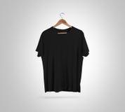 Κενό μαύρο μέτωπο μπλουζών στην κρεμάστρα, πρότυπο σχεδίου, πορεία ψαλιδίσματος Στοκ Εικόνα