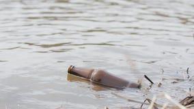 Κενό μπουκάλι μπύρας που επιπλέει στο νερό ποταμού Νερό και περιβάλλον ρύπανσης φιλμ μικρού μήκους