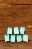 Κενό μπλε έγγραφο επτά με τις ζωηρόχρωμες καρφίτσες πέρα από το ξύλινο υπόβαθρο Στοκ Εικόνες
