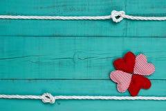 Κενό μπλε ξύλινο σημάδι με το κολάζ των κόκκινων καρδιών και σχοινί με τα σύνορα κόμβων Στοκ Εικόνες