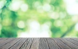 Κενό ξύλινο πάτωμα με το πράσινα bokeh και το φως του ήλιου Φυσική ανασκόπηση ομορφιάς Στοκ φωτογραφία με δικαίωμα ελεύθερης χρήσης