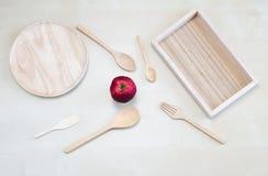 Κενό ξύλινο πιάτο, ξύλινος δίσκος, ξύλινο κουτάλι, ξύλινο δίκρανο, ξύλινο κουτάλι τσαγιού, ξύλινα σέσουλα και πορτοκάλι σε ένα κα Στοκ Εικόνα