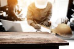Κενό ξύλινο tabletop πέρα από τον επιχειρησιακό μηχανικό που εργάζεται στο γραφείο του Στοκ Εικόνες