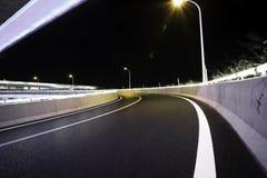 Κενό οδικό πάτωμα με τη γέφυρα οδογεφυρών πόλεων της νύχτας φω'των νέου στοκ εικόνα με δικαίωμα ελεύθερης χρήσης