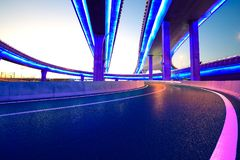 Κενό οδικό πάτωμα με τη γέφυρα οδογεφυρών πόλεων της νύχτας φω'των νέου στοκ φωτογραφία