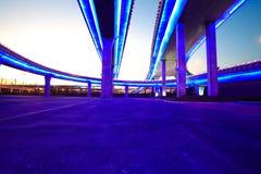 Κενό οδικό πάτωμα με τη γέφυρα οδογεφυρών πόλεων της νύχτας φω'των νέου στοκ εικόνες