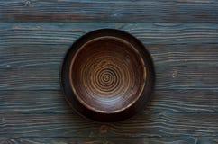 Κενό πιάτο αργίλου πέρα από το ξύλινο υπόβαθρο Στοκ φωτογραφία με δικαίωμα ελεύθερης χρήσης