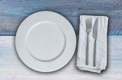 Κενό πιάτο με τα μαχαιροπήρουνα στο μπλε και άσπρο εκλεκτής ποιότητας ξύλο Στοκ Εικόνα