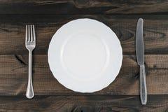 Κενό πιάτο με το δίκρανο και βουτύρου μαχαίρι στον ξύλινο πίνακα Στοκ εικόνα με δικαίωμα ελεύθερης χρήσης