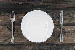 Κενό πιάτο με το δίκρανο και βουτύρου μαχαίρι στον ξύλινο πίνακα Στοκ φωτογραφίες με δικαίωμα ελεύθερης χρήσης