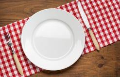Κενό πιάτο με το δίκρανο και μαχαίρι στο τραπεζομάντιλο Στοκ εικόνα με δικαίωμα ελεύθερης χρήσης
