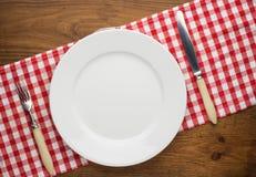 Κενό πιάτο με το δίκρανο και μαχαίρι στο τραπεζομάντιλο Στοκ φωτογραφίες με δικαίωμα ελεύθερης χρήσης