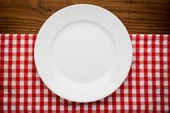 Κενό πιάτο με το δίκρανο και μαχαίρι στο τραπεζομάντιλο Στοκ Εικόνες
