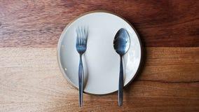 Κενό πιάτο με το κουτάλι και δίκρανο στο ξύλινο υπόβαθρο Στοκ Φωτογραφίες